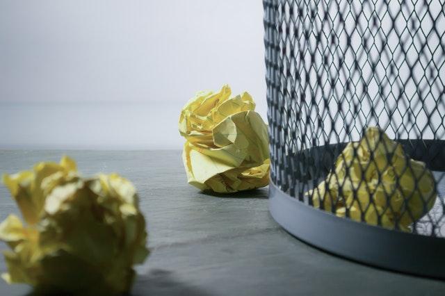 Fragment kosza na śmieci i pogniecione kulki papieru.