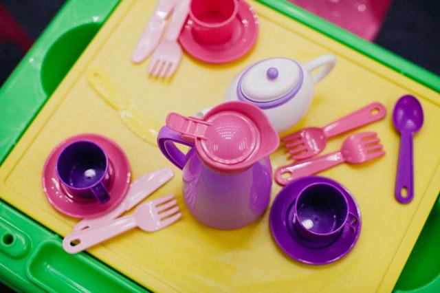Zabawkowe przybory kuchenne. Różowe noże i widelce, fioletowe filiżanki i dzbanek.
