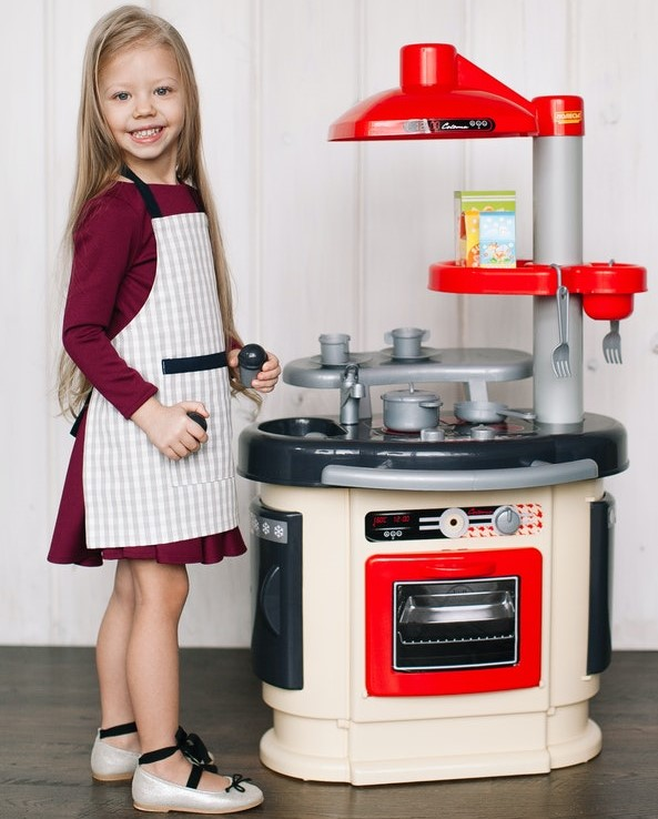 Dziewczynka bawiąca się plastikową kuchnią zabawkową.