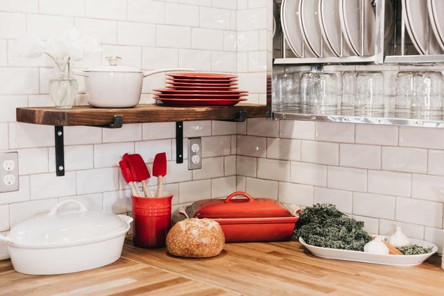 Róg blatu kuchennego, białe kafelki i czerwone akcesoria takie jak talerze, maselniczka i łyżki łyżki do mieszania.