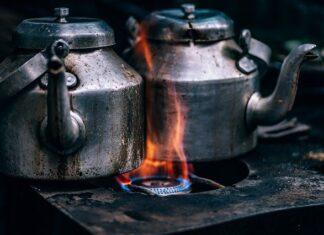 Dwa żeliwne czajniki gotujące się na żeliwnej kuchence, na ogniu.