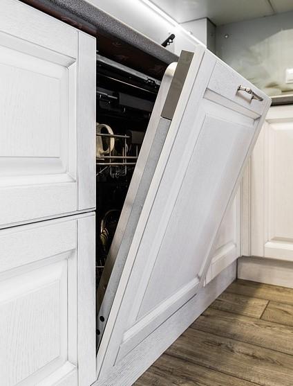 Otwarte drzwiczki do wbudowanej zmywarki. Białe szafki kuchenne.