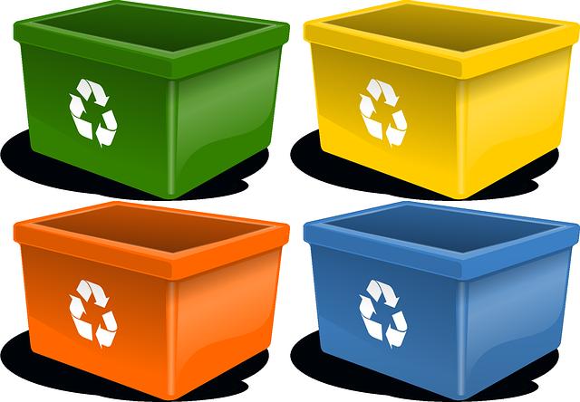 Cztery kosze na odpadki do recyklingu - zielony, żółty, pomarańczowy i niebieski.