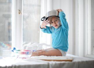 Dziewczynka w niebieskiej bluzie siedząca na blacie kuchennym z garnkiem na głowie.