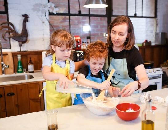 Mama z córką i synem gotujący w kuchni.