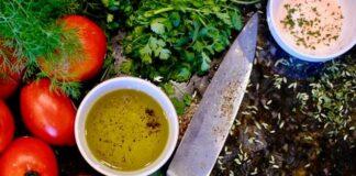 Nóż z czerwonymi pomidorami i miseczką z sosem.