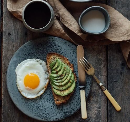 Talerz z jajkiem sadzonym i kromką chleba oraz kubki i sztućce.