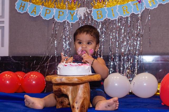 Małe dziecko jedzące tort. Balony i inne dekoracje.