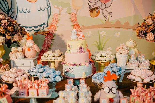 Tort urodzinowy, kolorowe babeczki ciateczka i inne przekąski urodzinowe.