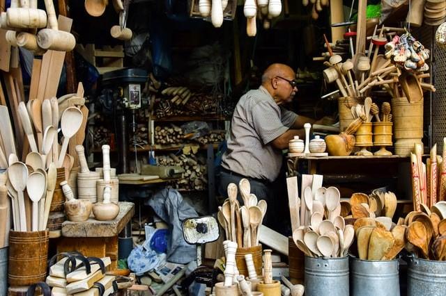 Sklep z drewnianymi przyborami kuchennymi i sprzedawca.