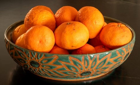 Ceramiczna, zielono-pomarańczowa misa z pomarańczami.