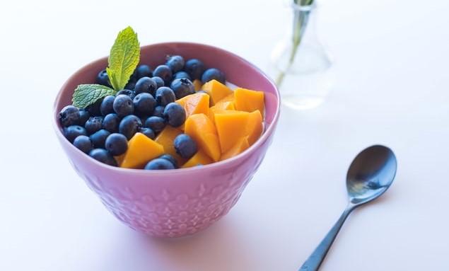 Różowa miseczka z owocami i łyżeczka.