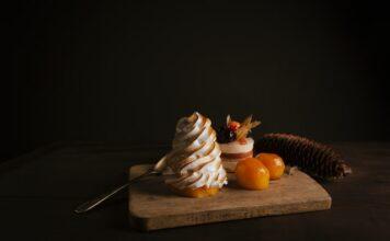 Deska do krojenia na czarnym tle, a na niej dwa ciastka z kremem, obrane brzoskwinie i łyżeczka