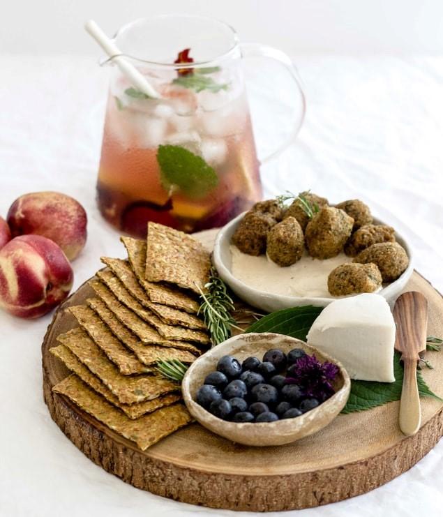 drewniana, okrągła, deska do krojenia, a na niej chlebki, borówki w miseczce, ser i oliwki.