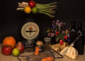 Stara waga kuchenna na czarnym tle, a na niej szparagi. Wokół leżą owoce i tarka.