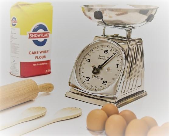 Analogowa waga kuchenna, jajka, łyżki, wałek do ciasta i mąka.