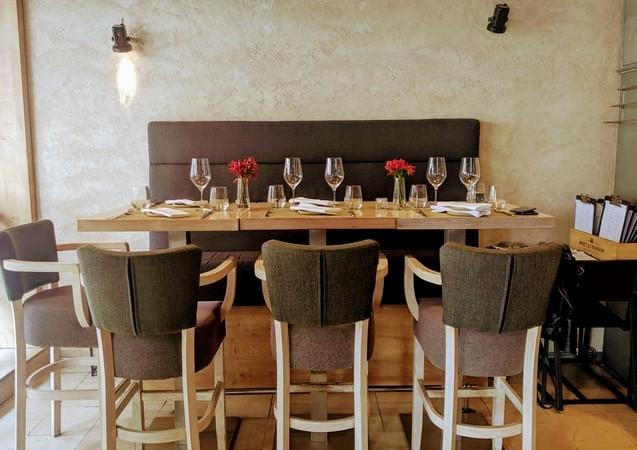Duzy drewniany stół, zastawiony kieliszkami, z ławką i szarymi krzesłami.