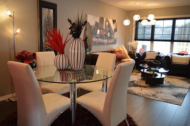 Salon ze szklanym, okrągłym stolikiem i czterema białymi krzesłami.