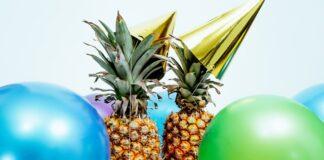 Zielone i niebieskie balony, a na środku dwa ananasy w złotych czapeczkach imprezowych.
