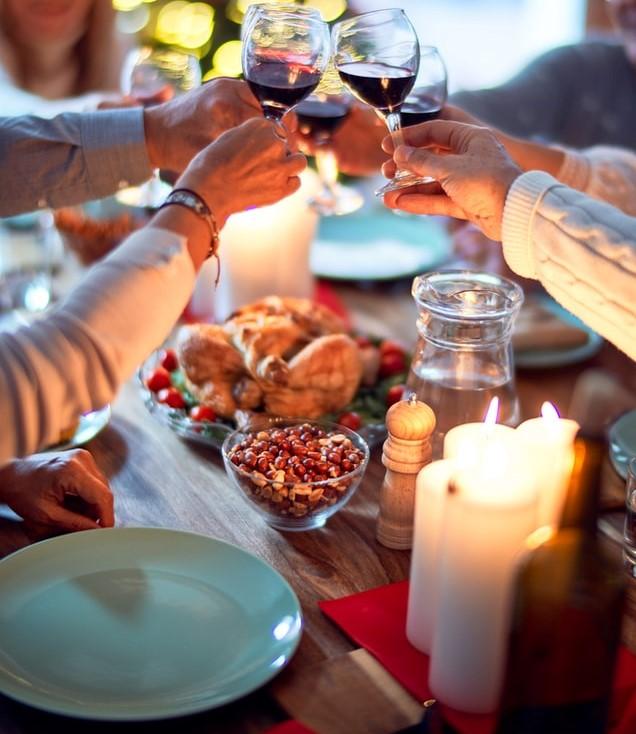 Stół ze świecami i jedzeniem oraz ręce wznoszące toast kieliszkami z winem.