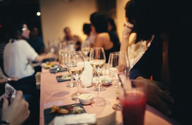 Zastawiony stół i ludzie wokół niego. Impreza w domu.
