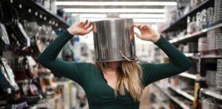 Dziewczyna z garnkiem na głowie, w sklepie z akcesoriami kuchennymi.