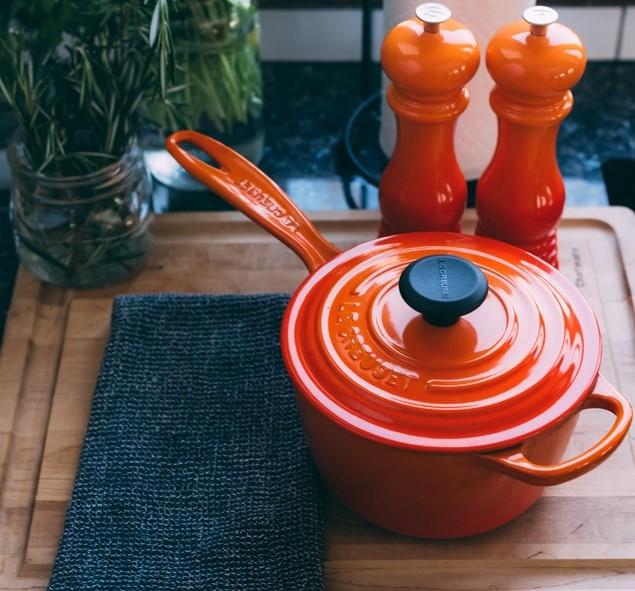 Pomarańczowy rondel na blacie kuchennym.