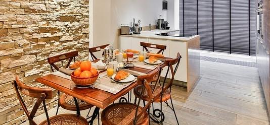 Drewniany, kuchenny stół z krzesłami zastawiony talerzami i misą z pomarańczami.