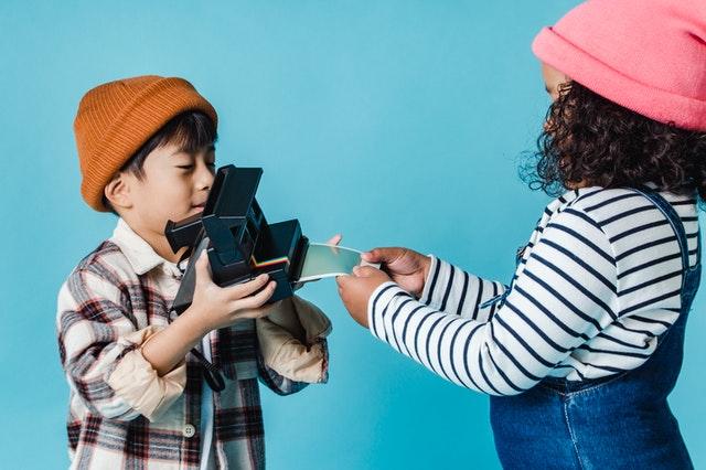 Dwoje dzieci bawiących się aparatem.