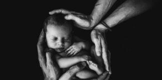 Noworodek trzymany w rękach przez mamę i tatę. Czarno białe zdjęcia.