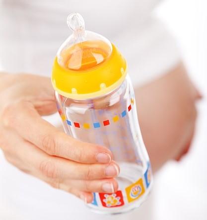 Kobieta w ciąży trzymająca butelkę ze smoczkiem.