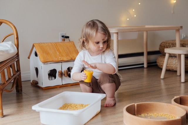 Mała dziewczynka bawiąca się w swoim pokoiku. Mały stolik i domek