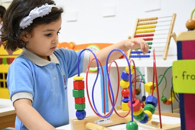 Dziewczynka bawiąca się drewnianą zabawka.