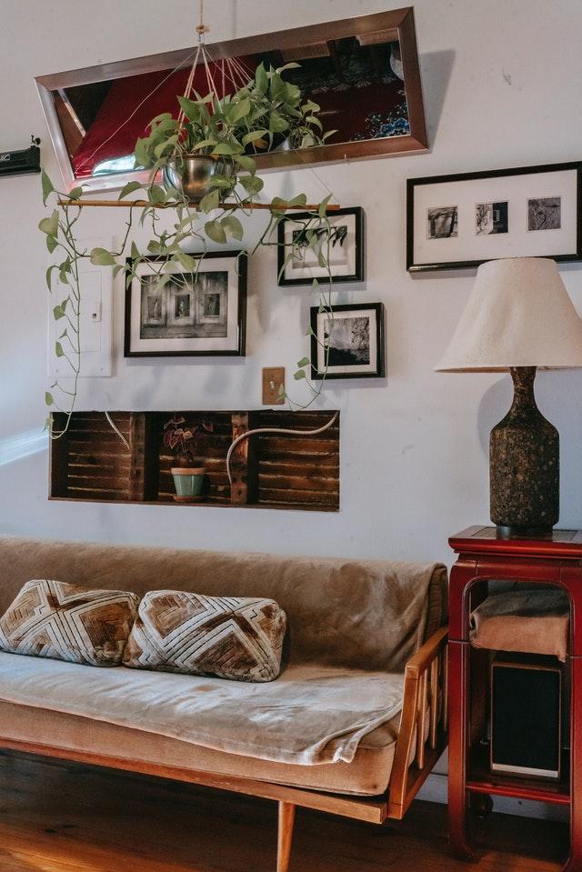 Salon z wieloma dodatami, poduszkami, lampą zdjęciami i kwiatami.