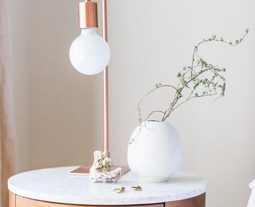 lampka i biały wazon na białym stoliku.