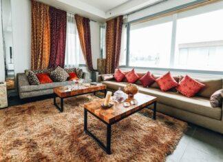 Salon z dodatkami - pomarańczowe poduszki, brązowy, włochaty dywan, zasłony i ozdoby na stoliku.