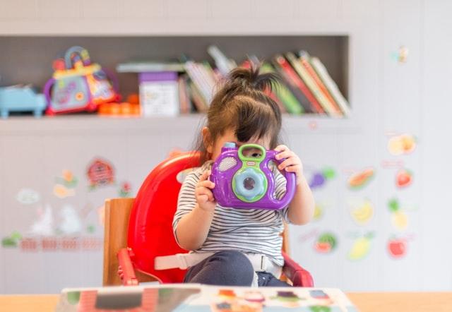 Mała dziewczynka bawiąca się fioletowym, plastikowym, aparatem.