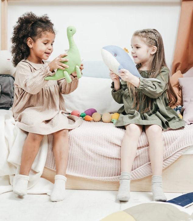 Dwie dziewczynki bawiące się zabawkami.