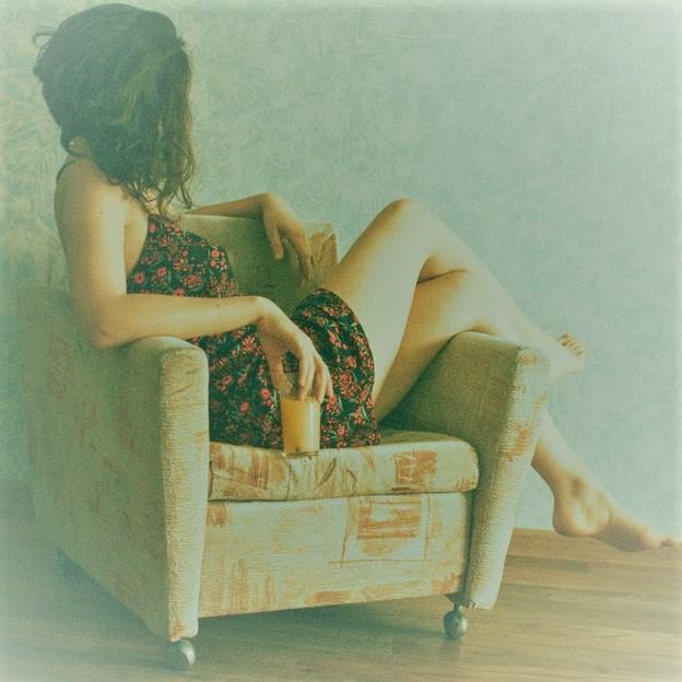 Dziewczyna siedząca bokiem na fotelu z nogami na podłokietniku.