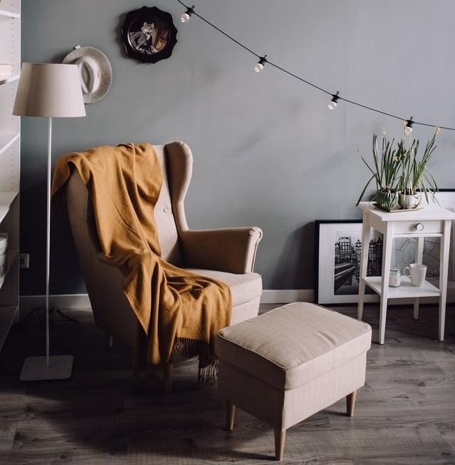 Beżowy fotel uszak z podnóżkiem.