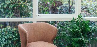 Różowy, nowoczesny fotel ze stolikiem kawowym i kwiatami w donicach.