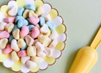 Kolorowe żelki na talerzach i różowy kubeczek.