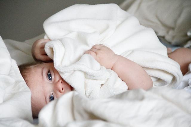 Male dziecko owinięte dużym, białym ręcznikiem.