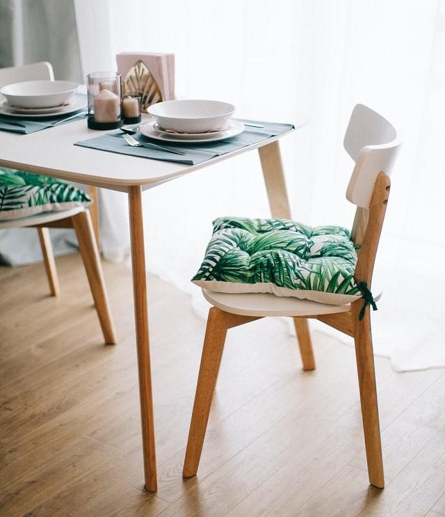 Biały stolik i białe krzesło z zieloną poduszką.