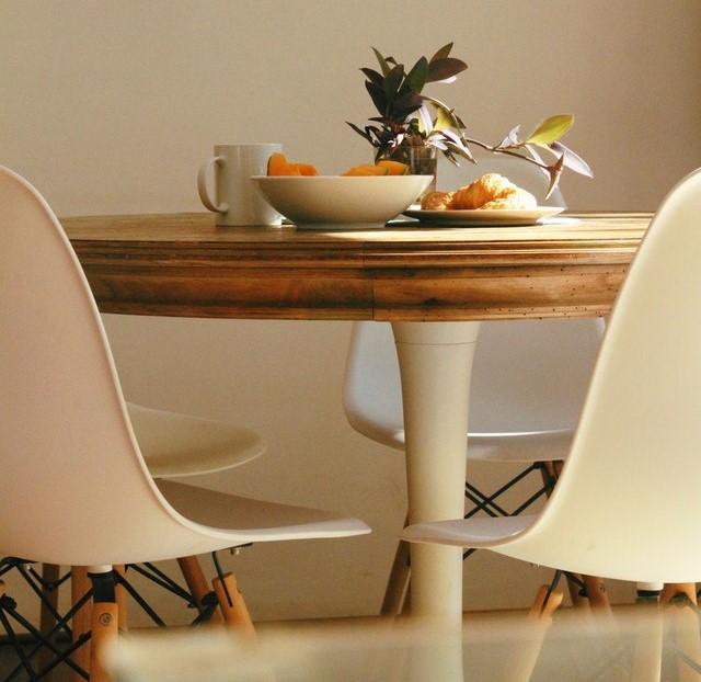 Białe plastikowe krzesła z drewnianym stołem.