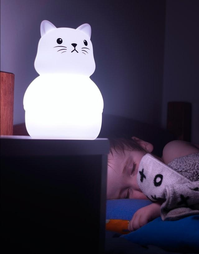 Lampka nocna w kształcie kota i śpiące dziecko.