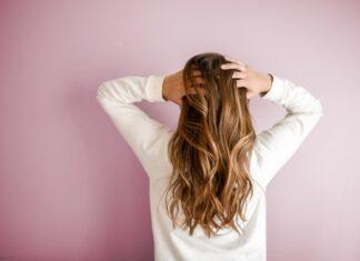 Dziewczyna z długimi, blond włosami, stojąca tyłem i bawiąca się nimi.