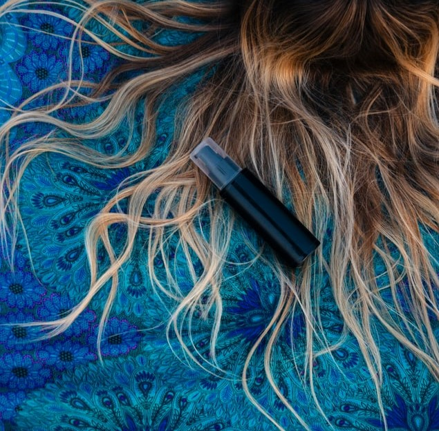 Długi, jasne, włosy rozrzucone na niebieskim kocu i czarna buteleczka.