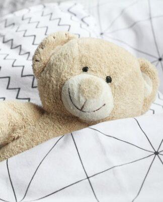 Biały pluszowy miś w łóżku