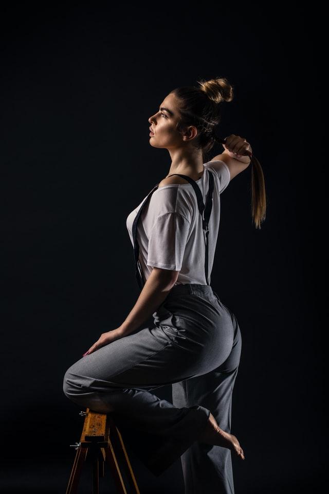 Dziewczyna na czarnym tle, trzymająca się za długi kucyk.